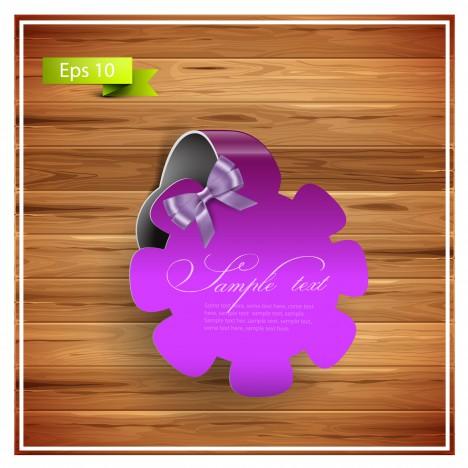 violet flower ribbon badge on wood background